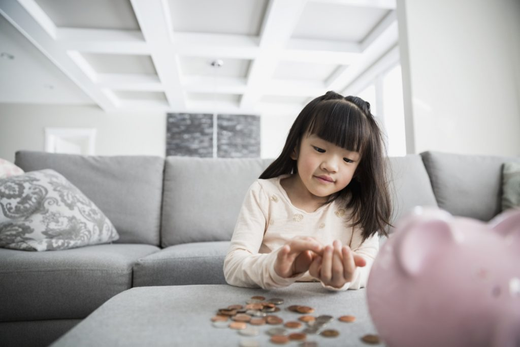 Girl counting coins from piggy bank in living room