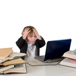 One small little girl (boy) wearing black suit and white shirt working on computer with books laying around on table. Isolated object.