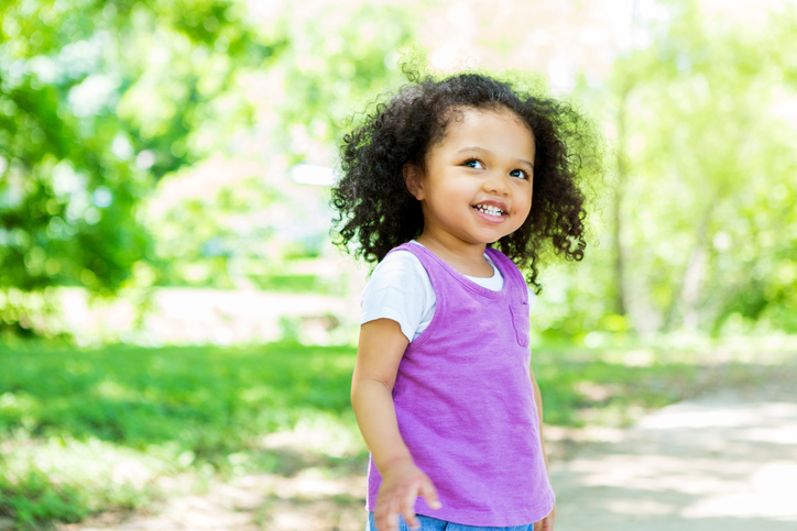 Pretty African American preschool age girl walks in the park on a sunny summer day. She is smiling as she walks. She has curly black hair and is wearing a purple shirt with white shirt underneath. She is walking on a footpath in the park.